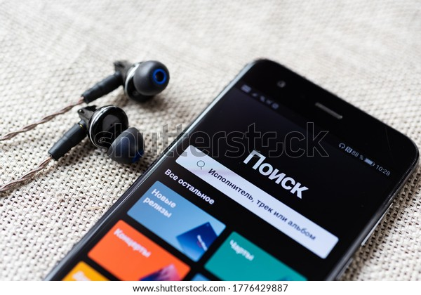 """Moscow,Russia 07.15.2020. Launch of the """"spotify"""" service in Russia. Mobile phone with interface and headphones."""