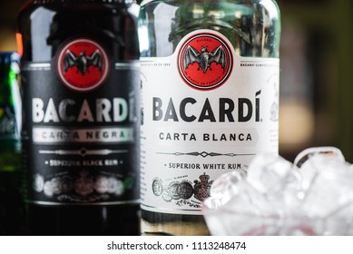 MOSCOW/RUSSIA - APRIL 24, 2018: Bacardi Superior Carta Blanca and Carta Negra rum bottles and glass with ice cubes. Bacardi Limited is sells more than million bottles of rum annually in 150 countries