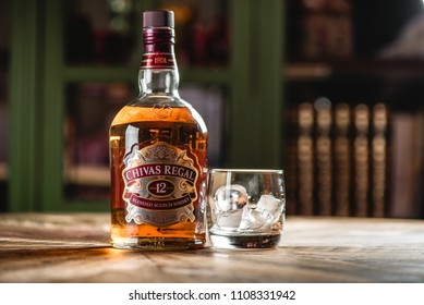 MOSCOW/RUSSIA - APRIL 24, 2018: Chivas Regal whiskey bottle and glass with ice cubes on wooden table in dark bar. Chivas Regal is famous brand of Scotch aged popular whiskey