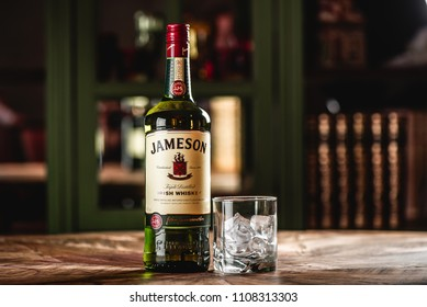 MOSCOW/RUSSIA - APRIL 24, 2018: Jameson whiskey bottle and glass with ice cubes on wooden table in dark bar. Jameson is a brand of traditional Irish whiskey from Dublin