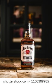 MOSCOW/RUSSIA - APRIL 24, 2018: Jim Beam bourbon bottle on wooden table in dark bar. Jim Beam is a famo?s brand of whiskey and the highest selling American bourbon in the world.