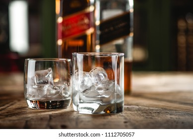 MOSCOW/RUSSIA - APRIL 24, 2018: Red label and Black label whiskey bottles and glasses with ice cubes on wooden table. Johnnie Walker is Scotch blended whiskey and one of famous brands in world