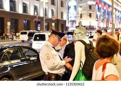 MOSCOW/RUSSIA - JULY 15, 2018: Russian policeman checks documents from a football fan on Moscow street in last day of International FIFA World Cup 2018. Time after final game Mundial 2018