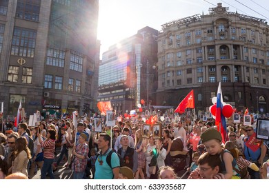 Moscow,Russia - May 9,2016: Immortal Regiment procession in Victory Day- thousands of people marching along toward the Red Square with flags and portraits in commemoration of soldiers of World War Two