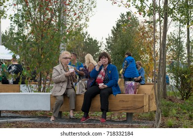 Moscow/Russia - September 18 2017: Women are sitting and eating ice-cream on a bench in Zaryadye Park