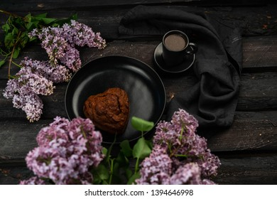 Moscow/Russia-CORCA 05.2019: an image of black coffee in a black cup, lilac flowers, on a dark wooden backdrop, homemade heart shaped cake, selective focus