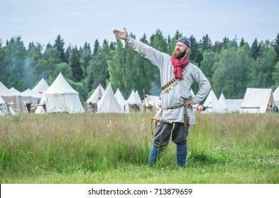 MOSCOW,RUSSIA-June 06,2016: Man in ancient peasant costume stands on green field of grass