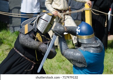 MOSCOW,RUSSIA-June 06,2016: Martial duel of two medieval teutonic warriors. Knights in full armour fight with swords on arena.