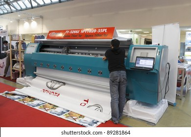 MOSCOW-SEPTEMBER 28: An official from the Chinese company Infiniti presents its printer, a printer for promotional materials, at the 2011 International Advertising Exhibition on September 28. 2011 in Moscow, Russia.