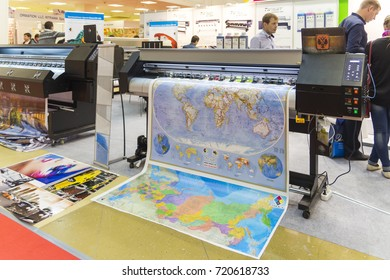 MOSCOW-SEPTEMBER 29, 2016: Business people are watching large format printer at the International Trade Fair Advertising