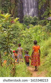 Moshi, Tanzania - 01/13/2019 - Group of children in bright clothing walking to high Materuni waterfall