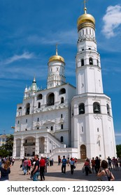 Moskow, Russia - Juny 23, 2012: Tourists walk on the Kremlin and look at Orthodox cathedral Uspenskiy in Russia
