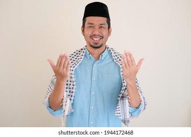 Moslem Asian man smiling while doing Islamic praying pose