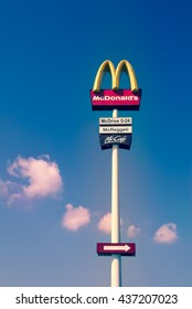 Mosonmagyarovar, Hungary - March 27, 2016:  McDonalds logo sign on very tall pole with blue sky and beautiful pinkish white clouds background