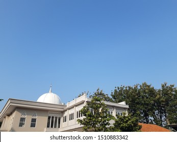 Mosque with blue sky background and green trees. Muslim praying house.