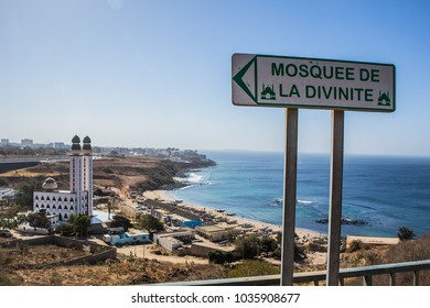 Mosque of divinity or mosquee de la divinite in Dakar, Senegal, behind a signboard leading towards the mosque on a sunny day. City of Dakar in the background.