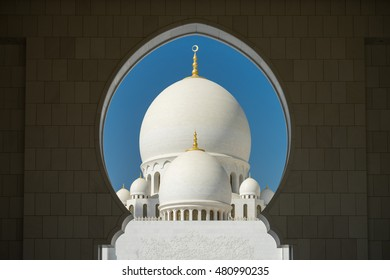 A mosque is framed by an arched passageway in Abu Dhabi, United Arab Emirates.