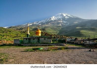 Mosque with golden roof underneath volcano Damavand, highest peak in Iran