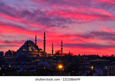 Mosque in Istanbul at sunset purple background. The view from the Galata Bridge.