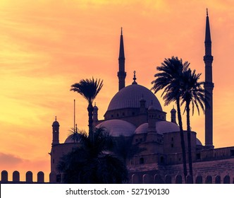 Mosque of Mohamed Ali in Saladin Citadel of Cairo at golden sunset. Silhouette of arabic city with minarets and palms in Egypt. Ancient landmarks of traditional muslim architecture in old town.