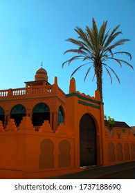 Mosque with red brick walls, with a large palm tree and a beautiful blue sky, Antsirabe, Madagascar, Indian Ocean.