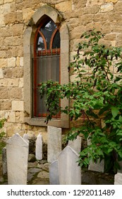 Mosque window with gravestones and pokeweed bush in hillside village of Yesilyurt, Malatya, Turkey - November 11, 2012