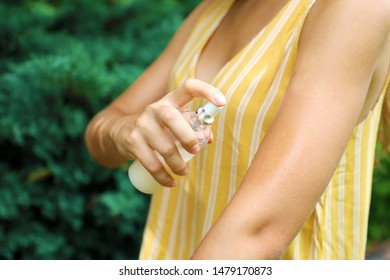 Mosquito repellent. Bug spray anti insects. Woman spraying insect repellent putting on skin outdoor in nature using spray bottle.