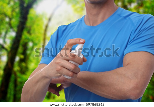 Mosquito repellent. Man using insect repellent spray from bottle in forest.