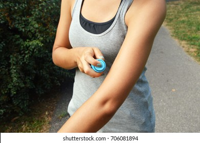 Mosquito repellent spray. Woman spraying insect repellent against bug bites on arm skin outdoor in nature forest using spray bottle.