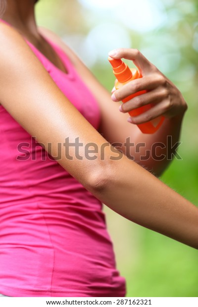 Mosquito repellent. Woman spraying insect repellents on skin outdoor in nature using spray bottle in forest.