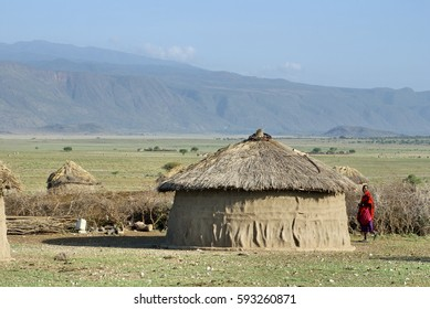 MOSQUITO RIVER, TANZANIA - CIRCA JANUARY 2014: Masai Mara man beside a rondavel house in a traditional village