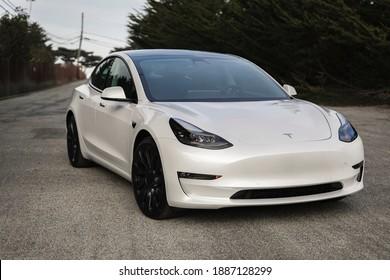 Moss Beach USA - January 1, 2021: Pearl white electric Tesla Model 3 dual motor performance AWD car with 20 inch Uberturbine wheels near San Francisco