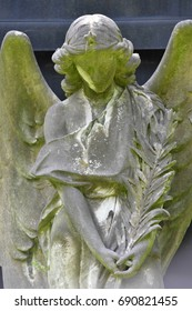 A moss covered sandstone sculpture of an angel.