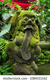 A moss covered statue of a funny god with long tongue in the Monkey Forest of Ubud, Bali, Indonesia
