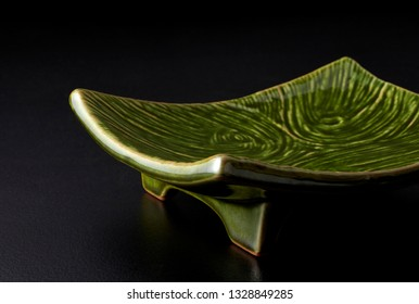 Moss green japanese plate on a black background
