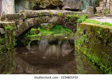 moss overgrown bridge over the millrace at the ruins of the old water mill at Dolny Mlyn in Bohemian Switzerland national park