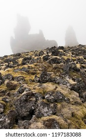 Moss and Rocks in the foreground with the rock formations of Londrangar, Iceland enshrouded in fog in the background.