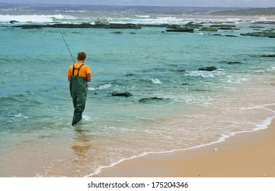 MOSSEL BAY, SOUTH AFRICA - JANUARY 19, 2014: Unidentified person fishing from the beach during high tide near Mossel Bay, South Africa Western Cape province, on January 19, 2014