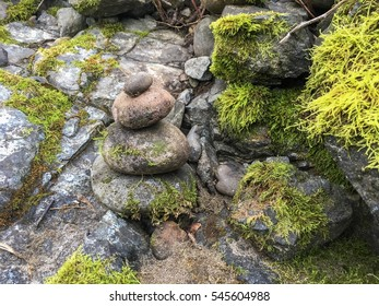 Mossy cairn on rocking terrain.