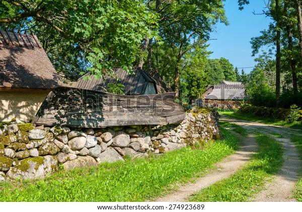 Mossy stone fence and old boat as decoration. Koguva village, Saaremaa island, Estonia, Europe