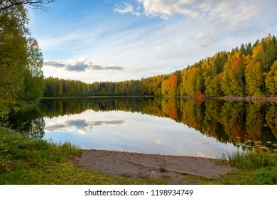 The most beautiful autumnal scenery in Finland. Colorful trees and reflecting water. Wallpaper with blue sky and vivid color forest.