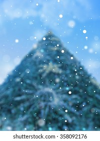 Most beautiful Christmas tree with ornaments receding into the distance high into the blue sky with clouds, snow falling white snowflakes.