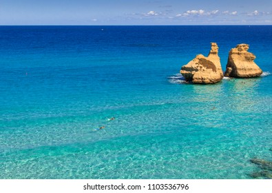 The most beautiful coast of Apulia: Torre Dell'Orso Bay, ITALY (Lecce).Typical seascape of Salento: view of the two stacks called The Two Sisters.Summertime: bathers swimming in the crystal clear sea.