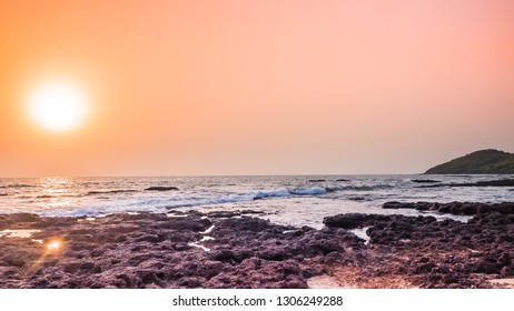 Most beautiful sunset at the sea in the northern Goa at Anjuna beach, India. The full sun of orange color sets behind the Arabian Sea with waves and rocks. Stunning tropical and exotic landscape.