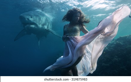 Most dangerous predator in The Ocean Great White Shark peaceful floating behind model posing underwater in fashion dress. Beautiful Model in deep sea in weightless condition hovering over coral reef.