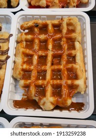 The most delicious Belgian waffles image. Tasty warm designed waffles with chocolate. Eating them on the city street is touristic lifestyle of big city. High resolution image in day time.