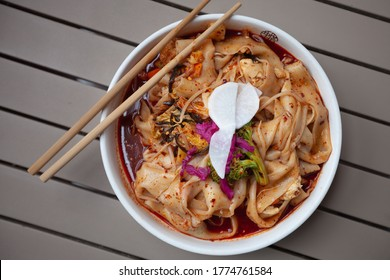 The most famous Chinese dish from Shaanxi province called biang biang noodles alternatively known as youpo chemian served with spicy chily oil chicken and fresh crunchy vegetables