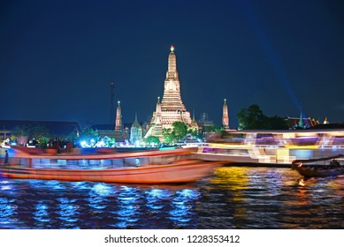Most famous landmark of Bangkok, Thialand. This is Wat Arun temple at night and service boats are moving in the Chaophraya river.