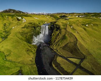 The most famous and one of the biggest waterfall in Iceland called Skogafoss. In summer the mountain covered with green glass. It is aerial view or top eye view. it is landmark and natural attraction