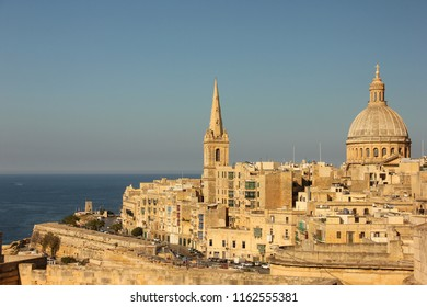 Most famous view of Valletta with Grand Harbour, Our Lady of Mount Carmel church's dome and tower of St. Paul's Anglican Pro-Cathedral during sunset strarting